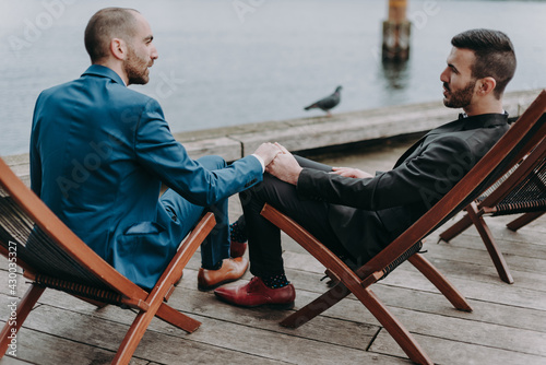 Foto A gay couple sits on deck chairs on the banks of a canal in Copenhagen holding hands