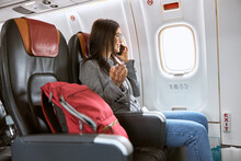 Happy Caucasian Female Passenger In Airplane Salon Before Fly