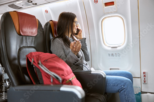 Happy caucasian female passenger in airplane salon before fly - fototapety na wymiar
