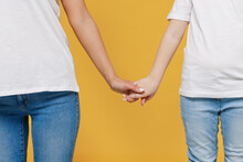 Close Up Cropped Woman In Basic White T-shirt Hold Hands With Child Baby Girl 5-6 Years Old. Mom Little Kid Daughter Isolated On Yellow Orange Color Background Studio. Mother's Day Love Family Concept