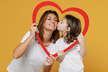 Happy woman in basic white t-shirt have fun with child baby girl 5-6 years old hold heart. Mom little kid daughter isolated on yellow orange color background studio. Mother's Day love family concept.