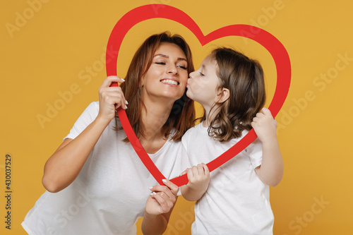 Fototapeta Happy woman in basic white t-shirt have fun with child baby girl 5-6 years old hold heart. Mom little kid daughter isolated on yellow orange color background studio. Mother's Day love family concept. obraz