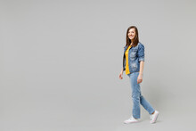 Full Length Side View Young Caucasian Woman 20s Wearing Casual Denim Jacket Yellow T-shirt Looking Camera Walking Going Strolling Isolated On Grey Background Studio Portrait People Lifestyle Concept.