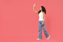 Full Length Side View Young Fun Smiling Happy Friendly Positive African American Woman 20s In Casual White Tank Shirt Walk Go Waving Hand Greeting Isolated On Pink Background People Lifestyle Concept