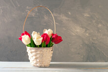 Wicker Basket Of Fresh Blooming Tulips Stands On Wooden Table