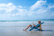 Asian man resting on sunbed on tropical beach. Happy guy sitting on beach chair by the sea using smartphone for selfie or video call. Handsome male enjoy beach outdoor lifestyle on summer vacation