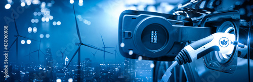 Vehicle EV electric car charge battery with wind turbine and blue sky blur bokeh on panoramic cityscape background. Idea nature electric energy to generate electricity. Green drive energy eco concept - fototapety na wymiar