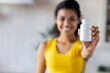 Happy young African American woman holding bottle of dietary supplements or vitamins in her hands. Healthy lifestyle concept