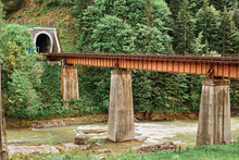 The Old Train Rail Above Mountain River Leading To Tunnel, Beautiful Landscape, Rail Road On The Bridge Near Water And Green Forest, Traveling Sightseeing.