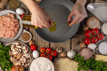 Chef Pours Oil On A Frying Pan For Frying. On A Background With Ingredients Mushrooms, Meat And Vegetables. View From Above