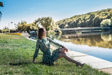 Elegant Woman In Fashion Dress Stands Near A Blue Lake In Sunny Summer Day