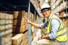 Portrait Of Smiling Asian Engineer Man Order Details Checking Goods And Supplies On Shelves With Goods Background In Warehouse.logistic And Business Export