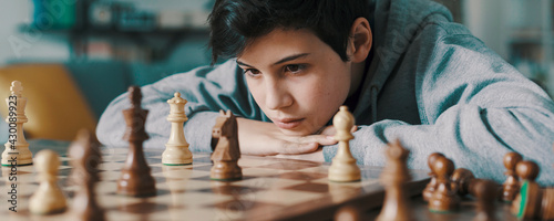 Fotografering Smart boy playing chess and staring at the chessboard