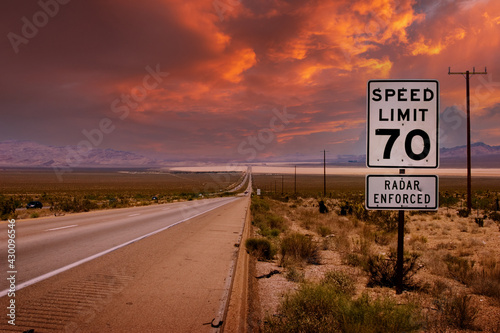Remote desert highway road to horizon at sunset, speed limit sign on a side. Nevada, USA.