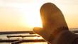 Rękawiczka na tle wschodu słońca nad morzem