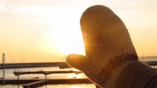 Obraz Rękawiczka na tle wschodu słońca nad morzem - fototapety do salonu