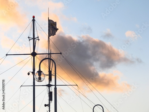 Obraz Maszt statku na tle obłoki przy wschodzie słońca - fototapety do salonu