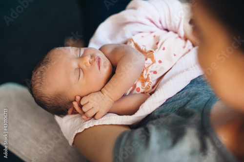 Fotografia Upper view photo of a caucasian mother holding her newborn kid on hands napping