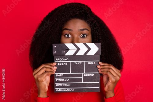 Fotografía Portrait of worried dark skin lady hold clapboard covering face eyes peeking iso
