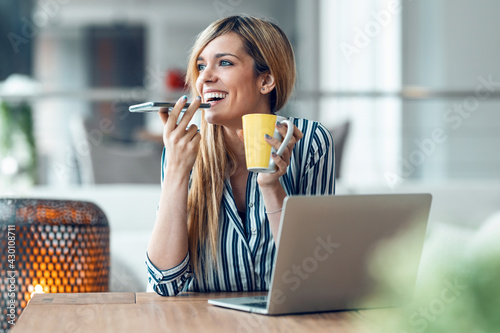 Fototapeta Smiling young woman sending audio message with her smart phone while drinking coffe in the office at home. obraz