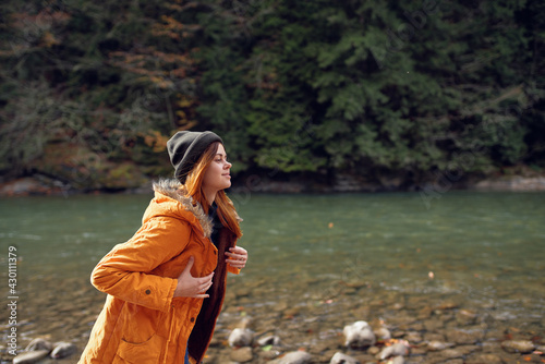 woman in a yellow jacket near the river mountains nature walk Fototapet