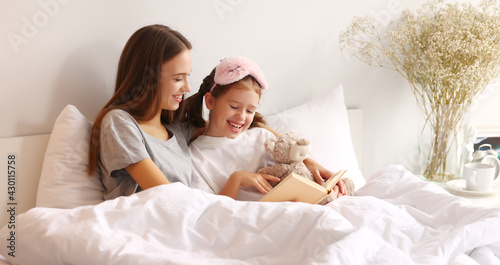 Fotografía Happy woman and girl reading book on bed in morning