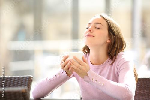 Woman holding coffee cup breathing fresh air in a bar - fototapety na wymiar