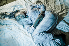 Young Sick And Depressed Afro American Woman In Pajamas Lying On Bed Suffering Menses And Period Pain Feeling Unwell Holding Her Stomach Sleepless At Night
