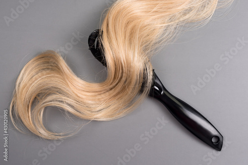 Fotografía Hairdresser professional hairbrush with curl of blonde hair on grey background
