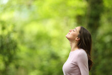 Relaxed Woman Breathing Fresh Air In A Green Forest