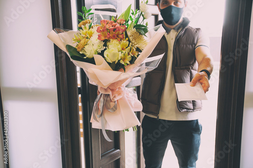 Obraz The delivery man delivers a bouquet of beautiful flowers to home - fototapety do salonu