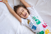 Funny Little Girl With Colored Handprints On A T-shirt.