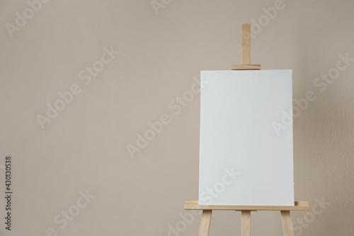 Slika na platnu Wooden easel with blank canvas on beige background