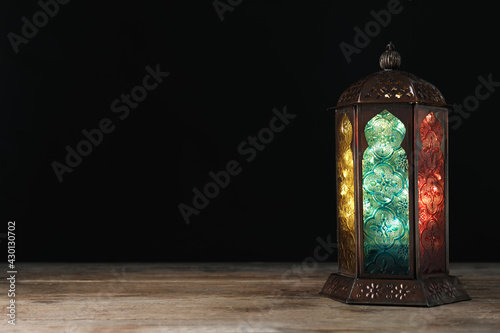 Obraz Decorative Arabic lantern on wooden table against black background, space for text - fototapety do salonu