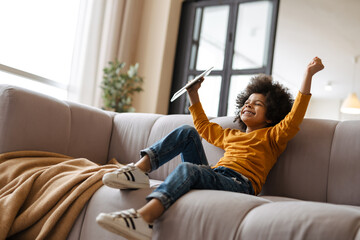 Black boy making fun and using tablet computer while sitting on sofa
