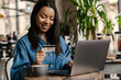 canvas print picture - Happy young african woman holding credit card
