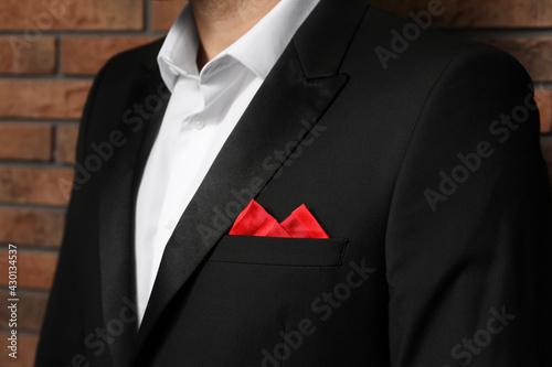 Obraz Man with handkerchief in breast pocket of his suit near brick wall, closeup - fototapety do salonu