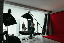 Professional Photographer Working In The Studio With A Male Model On A White Background.