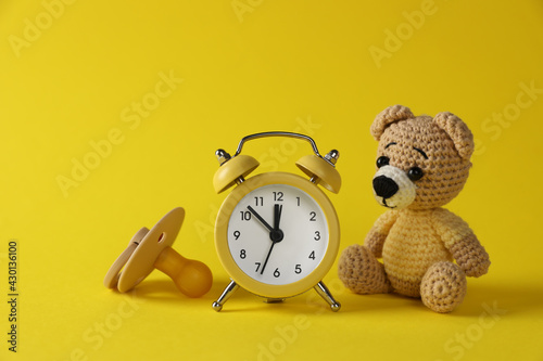 Fényképezés Alarm clock, toy bear and baby dummy on yellow background