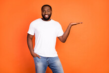 Photo Of Cheerful Happy Dark Skin Young Man Hold Hand Empty Space Advert Isolated On Orange Color Background