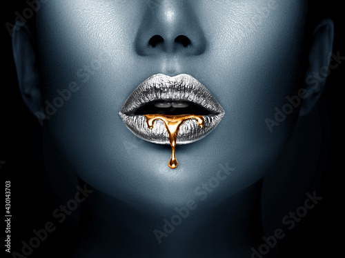 Lipstick dripping. Paint drips, lipgloss dripping from sexy lips, liquid Gold metallic paint drops on beautiful model silver girl's mouth, creative make-up. Beauty woman face makeup close up. Art