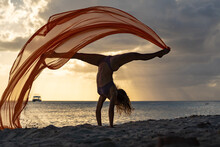 Silhouette Of Flexible Fit Woman Doing Handstand With Silk During Dramatic Sunset With Stormy Clouds On The Seascape Background. Concept Of Happiness, Freedom And Carefree.