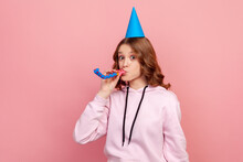 Portrait Of Happy Curly Haired Teenage Girl In Hoodie With Birthday Hat Blowing Party Horn, Having Fun At Holiday Celebration. Indoor Studio Shot Isolated On Pink Background