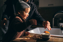 Cute Little Boy Peeling Citruses With Help Of Unrecognizable Father