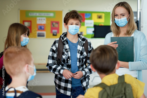 Teacher and children with face mask standing in the school - fototapety na wymiar