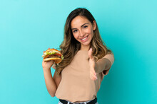 Young Woman Holding A Burger Over Isolated Background Shaking Hands For Closing A Good Deal
