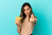 Young Woman Holding Fried Chips Over Isolated Background Making Money Gesture