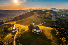 Sveti Andrej, Slovenia - Aerial Drone View Of Saint Andrew Church (Sv. Andrej) At Sunset In Skofja Loka Area With Blue And Golden Sky. Summer Time In The Slovenian Alps