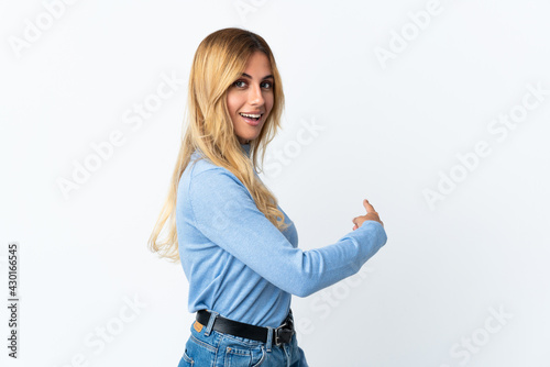 Fotografia Young blonde Uruguayan woman over isolated background pointing back