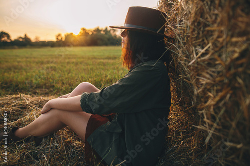 Fototapeta Beautiful stylish woman in hat sitting at haystacks in evening sunset in summer field